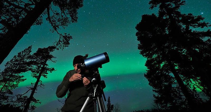 guy looking at aurora with telescope