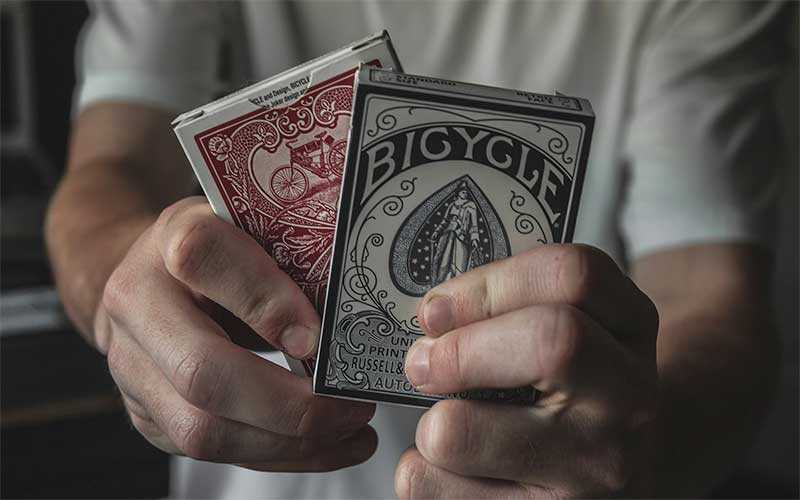 guy holding two decks of cards