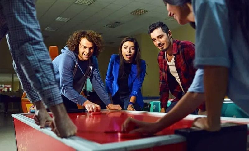 friends playing air hockey