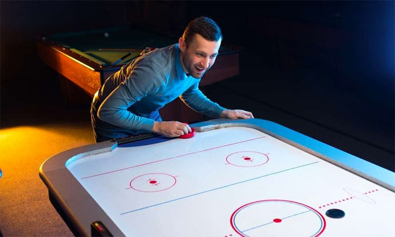 guy playing air hockey