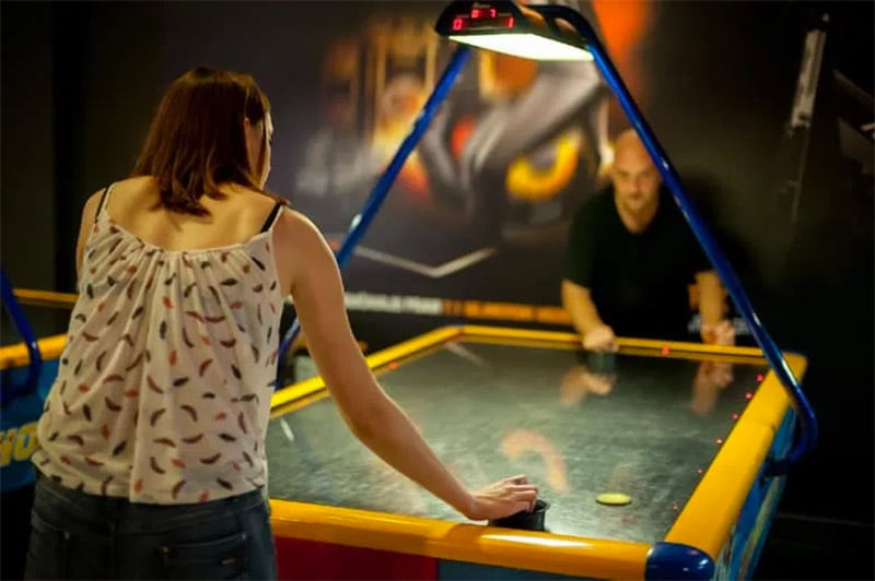 people playing air hockey